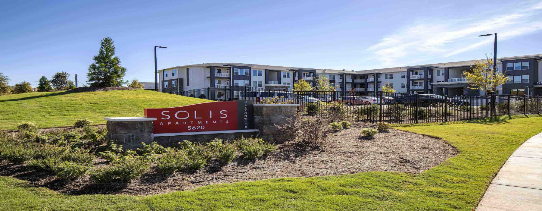 Solis Keltonwood front sign in a well-landscaped front area
